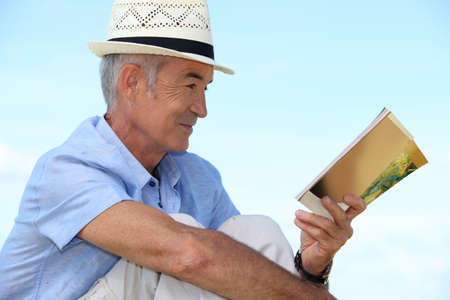 A mature man reading a book outside. photo
