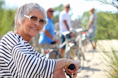 65 years old: 65 years old woman doing bike in the country with friends