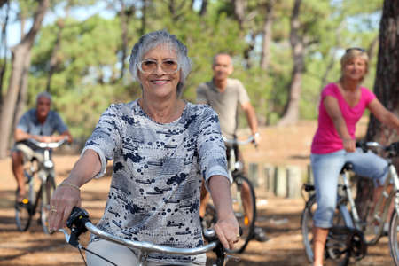 a 65 years old woman in first plan and three other people doing bike in the forest photo