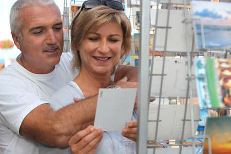 senior couple on vacation buying post cards photo