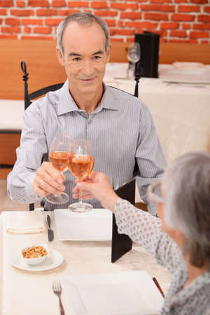 Senior couple drinking rose in a restaurant photo