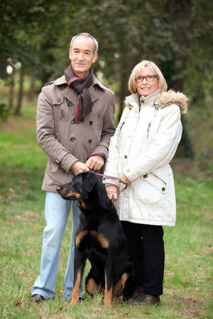 backwoods: mature couple walking in a park with their dog