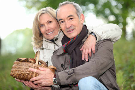 Couple collecting mushrooms in the forest Stock Photo - 11824315