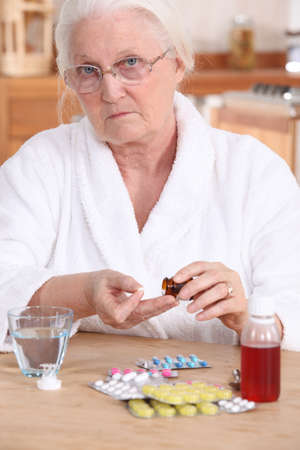Unhappy elderly lady taking her medication photo