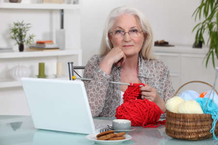 Elderly woman knitting by her laptop photo