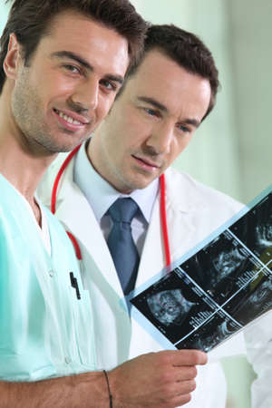 duo: male medical duo examining x-rays Stock Photo