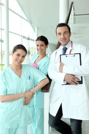 Doctor and two nurses standing on a staircase in a hospital photo