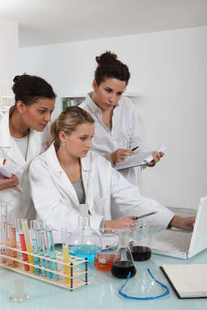 white coats: A team of female scientists examining the results of an experiment Stock Photo
