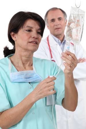 catheter: Doctor and nurse with IV drip Stock Photo