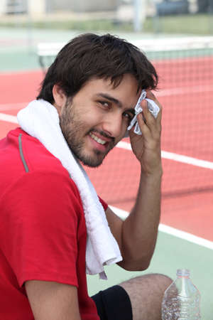 Tennis player mopping his brow on the sidelines photo
