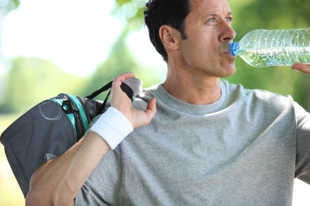 Athletic mature man drinking water from a bottle photo