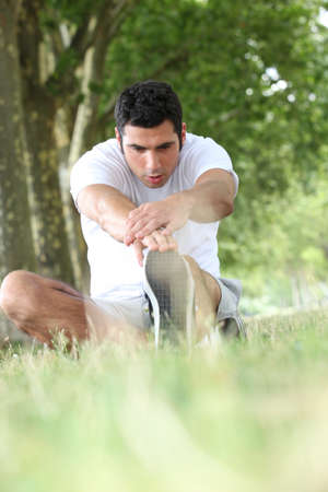Runner stretching on grass photo