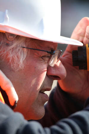 Land surveyor peering into an altometer photo