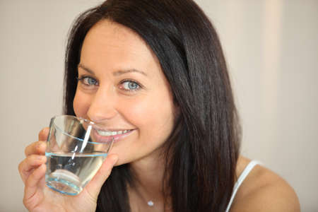 30 40: Brunette drinking a glass of water