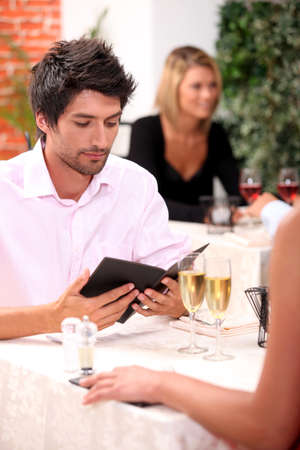 Young man looking at a menu in a restaurant photo