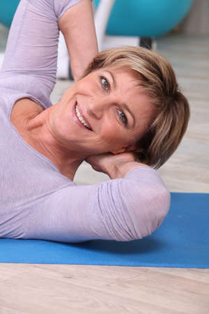 Woman doing sit-ups on a yoga mat Stock Photo - 11825587