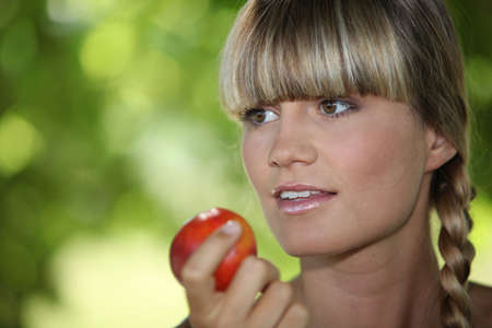 a blonde woman eating an apple photo