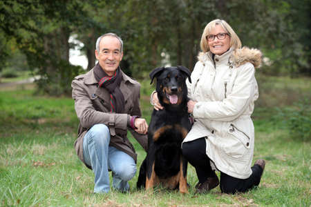 senior couple posing with their dog in a park photo
