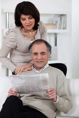 Man and woman reading newspaper photo