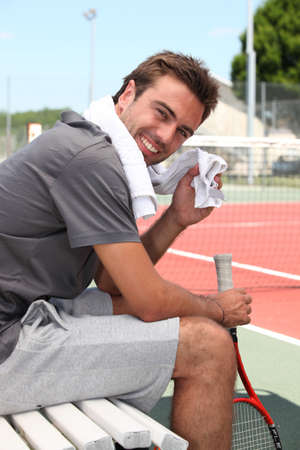 sweaty: Tennis player sat on bench