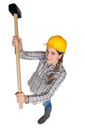 sledge hammer: A female construction worker holding a sledgehammer.