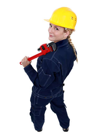 workwoman: Tradeswoman holding a pipe wrench
