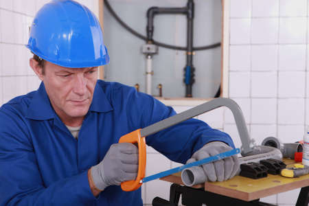 Plumber sawing plastic pipe photo