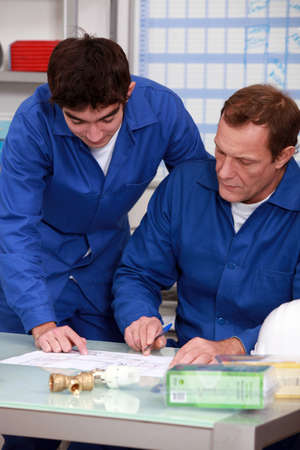 apprenticeship: blue collars in office: apprentice and instructor Stock Photo