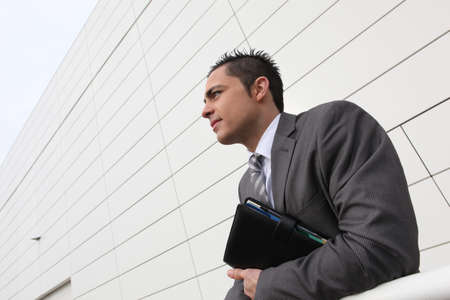 travelling salesman: Businessman stood outside building holding diary