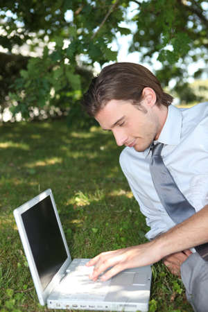 Smart male executive using a laptop with a blank screen in the park photo
