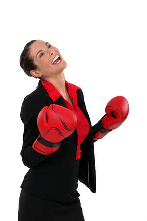 winning woman: ecstatic businesswoman with boxing gloves Stock Photo