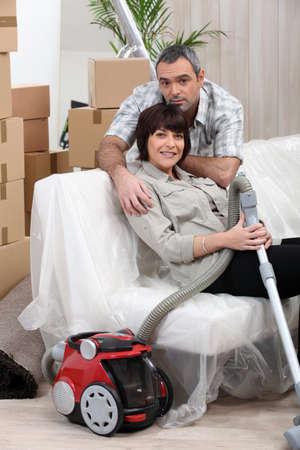 Couple vacuuming house before moving photo