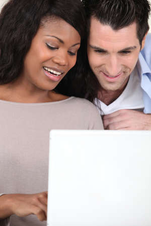 an interracial couple doing computer photo