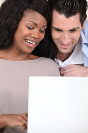an interracial couple doing computer photo