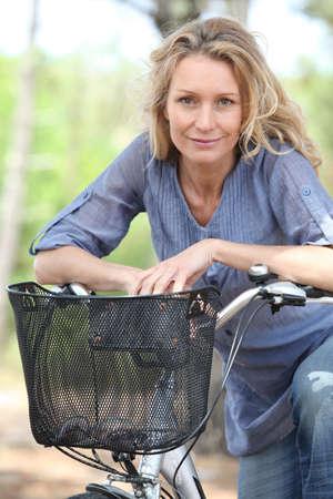 riding bike: Donna in bicicletta nella foresta