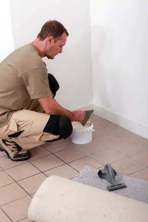 fitted: handyman putting glue and laying carpet Stock Photo