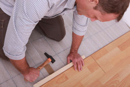 kneeling man: Man renovating the floor with a hammer