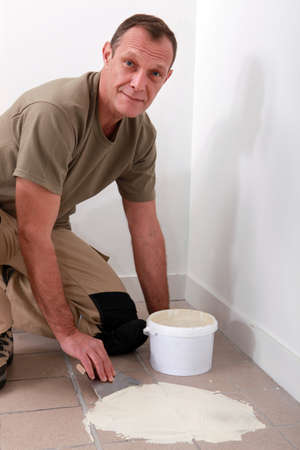 adherent: Handyman spreading adhesive over an old tiled floor Stock Photo