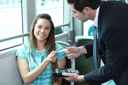 validating: A young female passenger showing her card to a controller on a bus or a tramway.