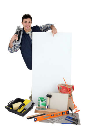 Young tiler pointing white board for message photo