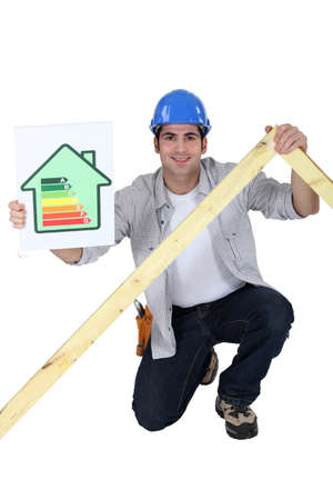 tradesperson: Tradesman holding a frame and an energy efficiency rating chart Stock Photo