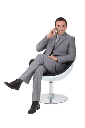director chair: Executive in a swivel chair talking on a cellphone Stock Photo