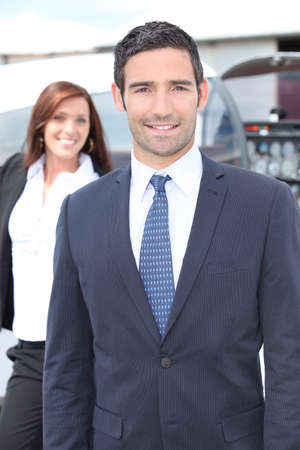 Businessman standing with a woman and light aircraft photo