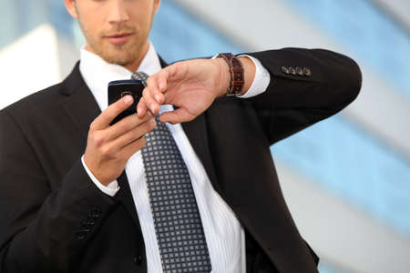 Young executive checking his watch against a cellphone photo