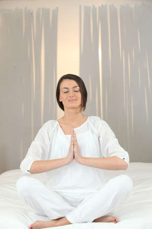 Woman meditating on a bed Stock Photo - 11842673