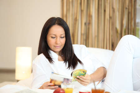 Woman reading a magazine over breakfast Stock Photo - 11842721