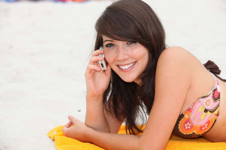 16 19 years: Girl on her cellphone on the beach Stock Photo