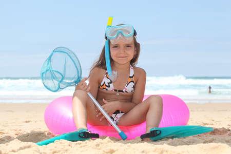 flippers: Niña en la playa con sentarse en boya con equipos de buceo
