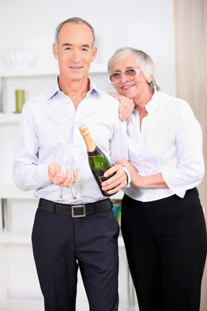 Old couple with a bottle of champagne photo