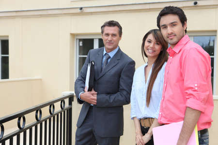 Couple standing outside a house with an estate agent photo